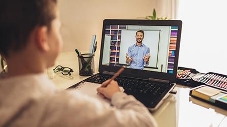 menino estudando na frente de um notebook com a imagem de um professor lecionando