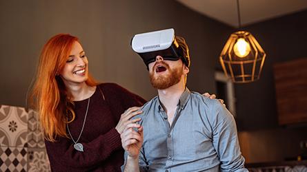 homem ruivo de camisa social inza utilizando um óculos de realidade virtual aumentada ao lado de uma mulher ruiva de blusa marrom que segura em seus ombros. O ambiente é parecido ai de uma sala de casa