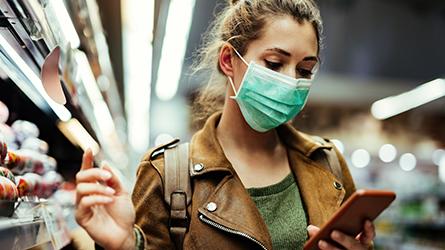 Mulher de máscara ao lado de uma gôndola de mercado, usando o celular