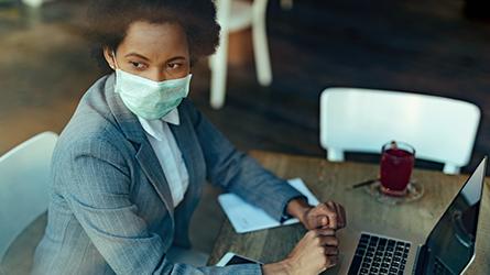 Mulher vestindo roupa social e usando mascara sentada em uma mesa em frente ao notebook