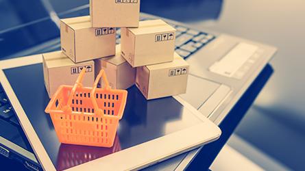 caixas de entre ao lado de uma cesta de compras em mimniatura sobre um tablet e um notebook