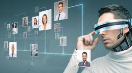 Foto de homem branco com um óculo de realidade virtual. Ele olha para um painel com várias fotos de pessoas.