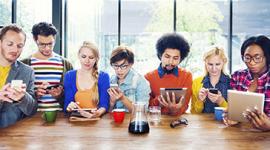 Foto. 7 pessoas sentadas em um mesa todas estão olhando para seus tablets ou celualres. são 4 mulheres e três homens e todos são jovens e estão com roupas despojadas como jaqueta jeans, camiseta.