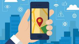 Imagem de uma mão segurando um celular. Ao fundo prédios e algumas nuvens, Na tela do celular está desenhado um ícone que indica a localização.