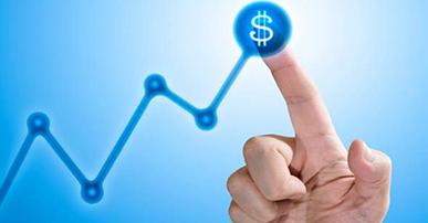 Gráfico em formato de linha azul e no pico mais alto, uma mão fechada com o dedo indicador levantado tocando nesse ponto. Nesse ponto também um símbolo de $. Imagem com fundo azul claro e linha do gráfico azul escuro.