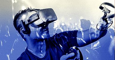 Foto. Homem de cabelo curto veste um óculos de realidade virtual. Em suas mãos ele está com sensores de realidade virtual também. Tanto o fundo da imagem como o homem estão com filtro azul.