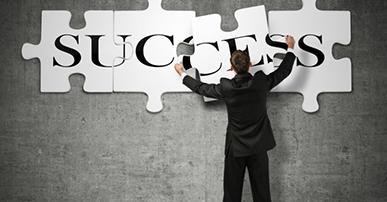 Foto de um homem de terno que está de costas. Ele monta um quebra-cabeça na parede com a palavra success. Ele está colocando a última peça com as letras CE da palavra success.