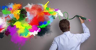 Foto. Homem com um lápis verde na mão desenhando em uma parede cinza. Ele está de costas, tem cabelo curto e usa blusa azul. Ele desenhou várias manchas de cores diferentes na parede.