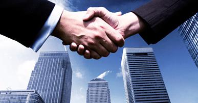 Foto. Aperto de mãos entre duas pessoas. Ambos estão com blazer escuros. Na imagem só aparece as mãos e uma parte dos braços. Na imagem também aparecem alguns prédios e no fundo o céu azul.