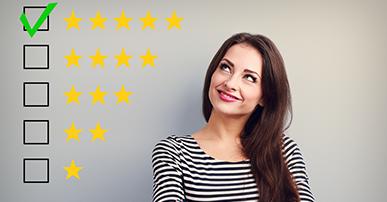 Foto. Mulher de cabelo comprido longo e castanho com blusa listrada, olha, levemente, pra cima. Do lado esquerdo da imagem o desenho de estrelas que simbolizam os números de 1 a 6 e indicam a aprovação do consumidor.