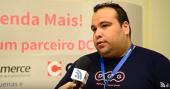 Foto. Do lado direito. Alexsandro Benitez, da DCG veste camiseta azul com o nome da empresa em rosa. Ele está com um crachá tem cabelos e olhos negros. Na frente dele vemos um microfone e um pedaço de uma mão segurando esse microfone.