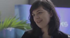 Foto em close da Ariane Maia da A2BI. ela tem cabelos negros até o ombro e olhos claros. Na frente dela nota-se um pedaço do microfone no qual ela fala. Atrás dela uma folha grande de uma planta e um banner azul.