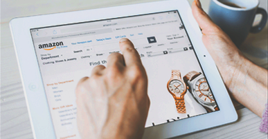 Mãos de uma pessoa branca segurando um tablet branco. Na tela do tablet está aberta uma pagina a Amazon e aparecem duas imagens de relógios um dourado e outro prateado. Próximo a mão da pessoa tem uma xícara de café azul.