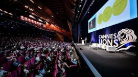 """Foto lateral de um auditório, plateia e palco. No palco, o logotipo do festival """"Cannes Lions"""", quatro bancos brancos e uma bancada. Próximo a bancada um homem de terno cinza está em pé. Atrás do palco e em cima do logotipo do festival, um painel grande com um slide."""