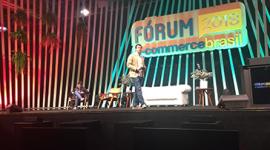 """Foto de uma palco. No fundo banner com o nome do evento """"Fórum E-commerce Brasil 2018"""" em azul e amarelo. Alguns arranjos de plantas penduradas no canto esquerdo do palco. Flávio Dias, CEO da Via Varejo no centro do palco, com calça azul e casaco beje. Atrás dele uma mesa do lado direito com um vaso de flores, ao lado um sofá branco e duas cadeiras. Sentado em uma das cadeiras está Léo Cid, da Accenture."""
