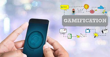 Foto apenas das mãos de uma pessoa do lado esquerdo, segurando um celular com a imagem de um globo terrestre. No lado direito, estão pequenos ícones que identificam o processo de gamificação e a palavra Gamification em cor cinza.