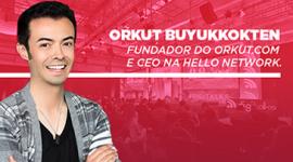 Foto. Criador do Orkut está na lateral esquerda da foto de braços cruzados. Ele veste blusa preta e casaco xadrez. Ao fundo a imagem de um palco e de uma platéia com fundo rosa. Na imagem está escrito o nome do Orkut e o cargo dele.