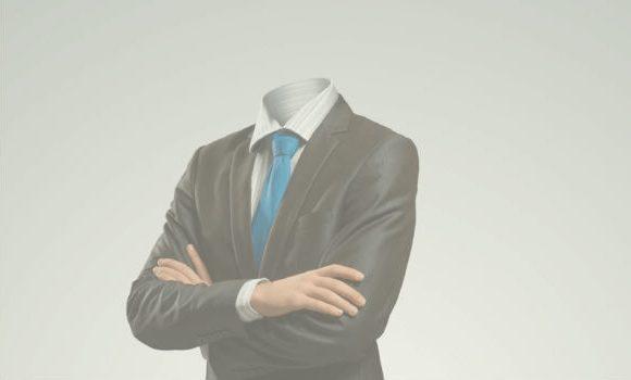 Foto. Homem de terno preto, camisa branca e gravata azul com os braços cruzados. Ele está sem cabeça.