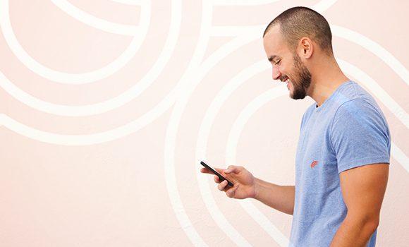 Foto. Homem de camisa azul com cabelo curto e barca está de perfil e segura um celular em sua mão.