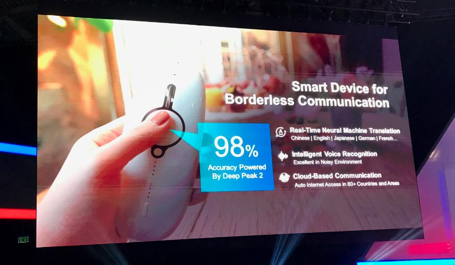Foto de slide com informações sobre o app translator. Uma mão segura o aparelho que é branco e tem uma espécie de botão no meio.