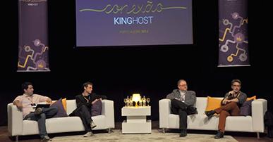 Quatro homens sentados em cadeiras que estão em cima de um palco. Atrás deles um telão com o nome do evento e dois banners verticais a cor roxa.