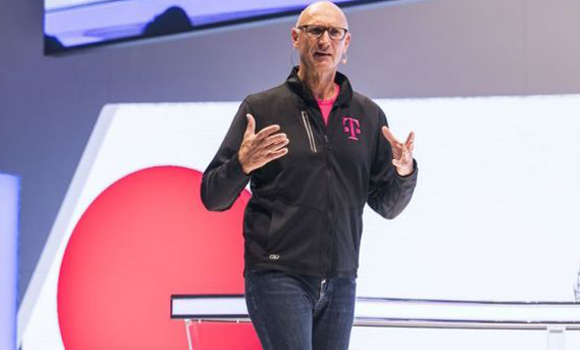 Foto. Homem de óculos, calça jeans e blusa de manga comprida preta está de pé em um palco e gesticula com as mãos. Atrás dele uma parece nas cores lilás, branca e vermelha.
