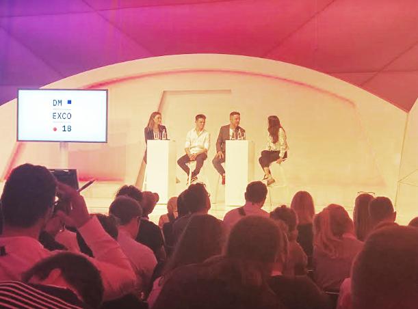 Foto. Duas mulheres e dois homens sentados em cadeiras em cima de um palco. Do lado esquerdo um telão com o nome do evento: dmexco 2018. Na frente deles uma platéia os assiste.