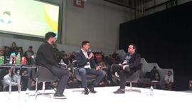 Foto. Três homens de calças e casacos escuros sentados em um palco. Ao fundo uma platéia e um telão.