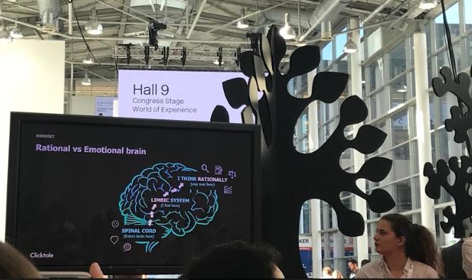 Foto. Mulher de cabelo enrolado preso e camisa branca, olha para uma tela que retrata o modelo do cérebro. Atrás da tela a imagem de uma árvore.