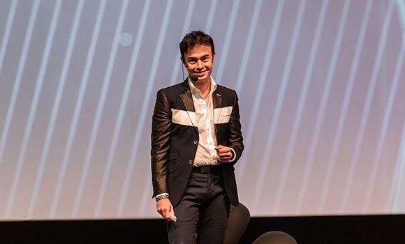 Foto do fundador do Orkut. Ele usa calça preta, camisa branca e casado preto.