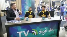 Foto. Flávio, Digitalks, Leandro, Apiki e Felipe da Hedgehog estão sentados em cadeiras e na frente deles tem a bancada da TV Digitalks com o símbolo da TV Digitalks.Todos estão com microfones na mão.