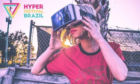 Foto. Mulher loira de cabelo um pouco acima do ombro, veste camiseta vermelha e usa um óculos de realidade virtual. Ela está segurando o óculos com suas mãos. Do lado esquerdo da imagem está escrito o nome do evento: Hyper (na cor rosa) Festival (cor amarela) e Brazil (cor azul).