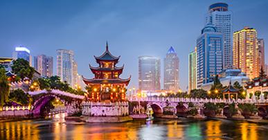 Foto. Ponte iluminada com prédios atrás. Na frente da ponte, do lado esquerdo da imagem, uma construção típica chinesa. A ponte está em cima de um rio e a foto da cidade foi tirada à noite.