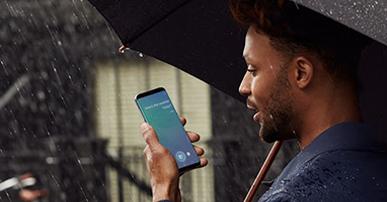 Foto. Homem negro, veste camisa azul, segura um guarda-chuva com uma das mãos e o celular com outra.