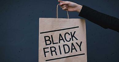 Braço de uma mulher que veste uma camisa preta e segura uma sacola de papelão na mão. Na sacola está escrito black friday em letras pretas.