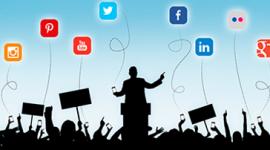 Imagem. Sobra de pessoas em uma platéia, algumas seguram cartazes e um homem, que também só vemos a sombra, está no palco em frente a um palanque. No fundo um céu azul e os ícones de algumas redes sociais como linkedIn, facebook e twitter.