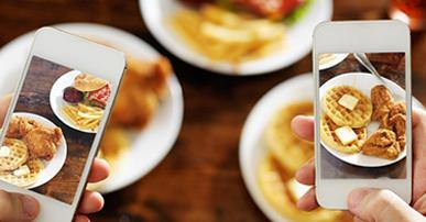 Foto. Três pratos de comida brancos e segundo plano. Duas pessoas seu segurando seus celulares e na tela dos celulares aparece o prato de comida mais nítido.