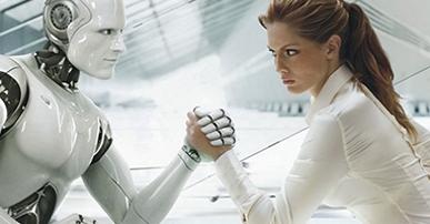 """Foto. Um robô branco que imita o corpo humano está frente a frente com uma mulher de blusa branca, cabelos castanhos preso e olhos castanhos, Ambos estão sérios e estão disputando """"braço de ferro"""". Atrás deles um ambiente de uma sala toda branca."""