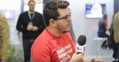 Foto. Roberto Rocha, da LeadLovers, veste camiseta vermelha clara com letras brancas. Ele segura um microfone com a canopla do digitalks e está sentado em uma bancada. Atrás dele observa-se o ambiente do evento.