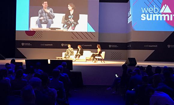 Foto. Palco do Web Summit e 3 pessoas sentadas em cadeiras no palco. Atrás deles dois telões. Na frente deles pessoas sentadas na platéia.
