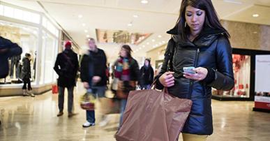 Foto. Mulher com traços japonês. cabelo liso e olhos puxados, usa calça amarela e casaco preto. Ela está parada em um shopping, segurando duas sacolas e olhando o celular. Atrás delas algumas lojas e pessoas circulando pelo local.