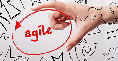 Foto. Mão de uma pessoa branca, envolvendo um círculo vermelho com uma seta. Dentro está escrita a palavra agile. Ao redor desse círculo e da mão alguns desenhos em preto.