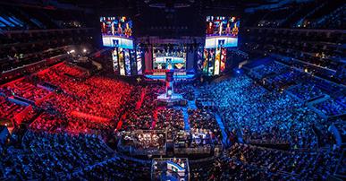 Foto. Um estádio lotado de pessoas, sob as pessoas uma luz vermelha e outra azul. No fundo o palco bem grande com 3 telões.