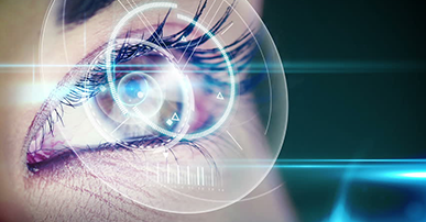 Foto. Olho castanho de uma mulher, cílios bem definidos. O olho está envolto por um círculo que representa um sistema tecnológico.