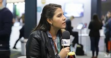 juliana fragoso tem cabelo liso comprido e preto, ela veste camisa azul e jaque de couro preta. Ela está sentada e segura um microfone. Atrás dela um ambiente de evento.