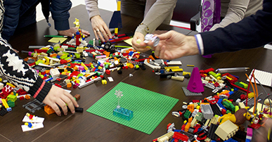 Foto. Mãos de pessoas sob uma mesa segurando peças de lego. Em cima da mesa várias peças de lego espalhadas.