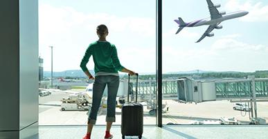 Foto. Mulher com calça jeans, tenis vermelho e blusa de frio verde, está parada no aeroporto, olhando pela janela e segura uma mala de rodinha. Na janela um avião passa do lado direito e temos a vista da pista do aeroporto.