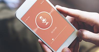 Foto. Mãos de um homem segurando um celular branco com uma tela laranja e um símbolo de microfone. Ele está ouvindo um podcast.