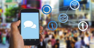 Foto. Mão segurando um celular com uma tela azul e o desenho de um balão. Ao fundo pessoas desfocadas e, desenhado na foto os símbolos de algumas redes sociais.