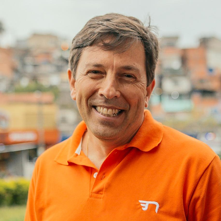 Foto: João Amoêdo sorrindo com camisa laranja e fundo desfocado.